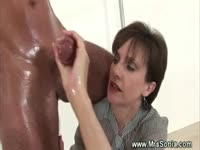 Mature dominatrix gives a tied up guy an oily hand and blowjob